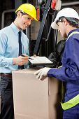 Young male supervisor showing clipboard to mid adult foreman at warehouse