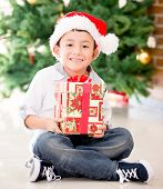 Happy boy holding a Christmas gift and smiling