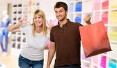 Man Holding Shopping Bag Inf ront Of Happy Woman, Indoors