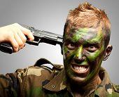 Soldado poner bala en la cabeza contra un fondo gris