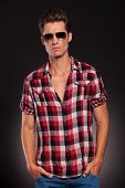 attractive man dressed casually in a  shirt stading with hands in his pockets, wearing sunglasses