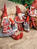 Two christmas rag dolls sitting and standing on an burlap background