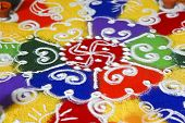 stock photo of swastik  - Multi colored patterned rangoli design a ritual performed by hindus generally during the hindu new year and divali along with the light of diwas - JPG