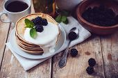 stock photo of whipping  - A stack of fresh homemade pancakes with blackberries and whipped cream on a wooden table a healthy breakfast close-up.