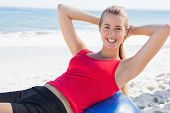 Fit blonde doing sit ups on exercise ball on the beach