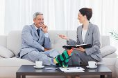 Funny businessman wearing stripey socks and laughing with his colleague sitting on sofa