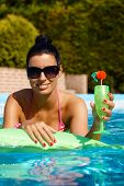 Attractive woman with cocktail in swimming pool, smiling.