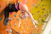 Girl with climbing equipment hanging on a rope up the face on the climbing gym
