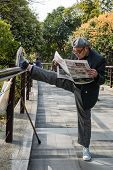 SHANGHAI - APRIL 7: one old man exercising stretching splits and reading newspaper in gucheng park