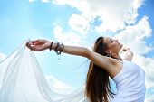 Happy young woman holding white scarf with opened arms expressing freedom, outdoor shot against blue
