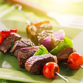 stock photo of braai  - grilled beef shishkabobs on green plate - JPG