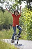 stock photo of unicycle  - Boy balancing on a unicycle in the park - JPG