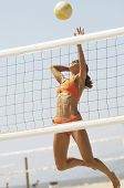 foto of volleyball  - Female beach volleyball player jumping to spike volleyball over net - JPG
