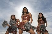 Happy multiethnic cheerleaders dancing with pom poms against the sky