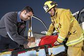 stock photo of accident victim  - Side view of a fire fighter and paramedic assisting man at crash site - JPG
