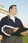 Coach with clipboard standing by running track