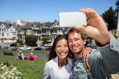 Happy young couple in San Francisco Alamo Square taking self-portrait photo pictures with smart cell