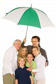 Three Generations Family Standing Isolated On White Background Holding Umbrella