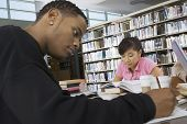 Two multiethnic students studying in the college library