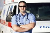 stock photo of paramedic  - Portrait of a confident male paramedic worker standing in front of an ambulance - JPG