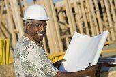 Porträt eines lächelnden Reifen Mannes im Hardhat Betrieb Blueprint vor Haus-Baustelle