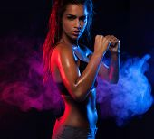 Determined fit sexy woman working out on blue and violet smoky wave background