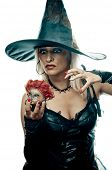 Pretty blonde in the witch costume holding doll head and casts a spell
