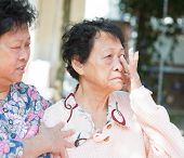 stock photo of condolence  - Sadness senior woman wiping off her tears in eyes - JPG