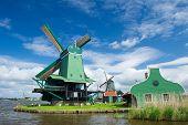 Green windmill at the Dutch Zaanse Schans near the river