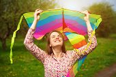 Happy woman is fling a kite on a spring meadow