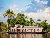 stock photo of alleppey  - House boat in backwaters at palms background in alappuzha Kerala India - JPG
