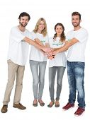 Group portrait of happy volunteers with hands together over white background