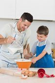 Happy father pouring milk in bowl while baking cookies with son at kitchen counter