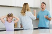 foto of pointed ears  - Frustrated little girl covering ears while parents arguing in kitchen - JPG