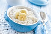 stock photo of cereal bowl  - Oatmeal with banana in a bowl on a table - JPG