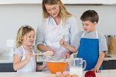 Children and mother baking cookies at counter top in kitchen