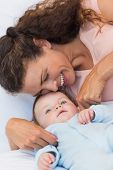 stock photo of tickle  - Happy mother tickling baby boy in bed - JPG