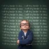 image of discipline  - Naughty schoolboy with lines written on a blackboard reading I will try harder in class - JPG