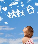 stock photo of daydreaming  - Young girl daydreaming with family and household clouds on blue sky - JPG