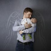 Father leaning against wall with painted angel wings, holding sleeping newborn baby, smiling affectionately.