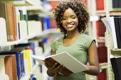 stock photo of librarian  - smiling female african american student in university library - JPG