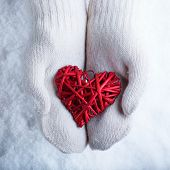 Female hands in white knitted mittens with a entwined vintage romantic red heart on a snow backgroun