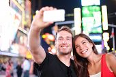 Dating young couple happy in love taking selfie self-portrait photo on Times Square, New York City a