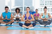 stock photo of namaste  - Sporty young people in Namaste position with eyes closed at a bright fitness studio - JPG