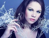 stock photo of cold-shoulder  - Young woman with winter twig. Portrait in cold tones.