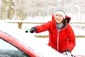 foto of ice-scraper  - A picture of a young woman cleaning a windshield from the snow - JPG