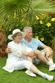 Elder couple sitting near flowers