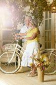 Elderly couple with bicycle on veranda