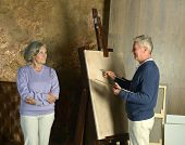 Elderly couple painting with easel