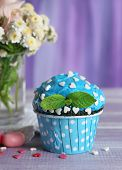 Tasty cupcake on table, on fabric background
